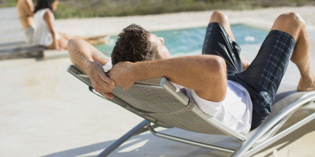 Man relaxing in lounge chair at poolside