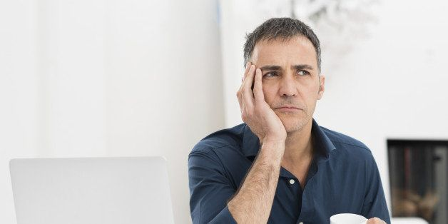 Portrait Of A Worried Mature Man With Laptop Holding Cup