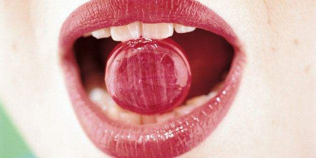 Mouth of woman biting candy
