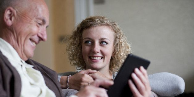 Senior man and smiling woman using digital tablet