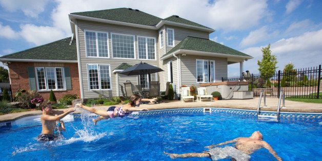 Family playing in backyard pool