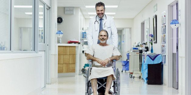 Happy doctor pushing disabled man in wheelchair at hospital corridor
