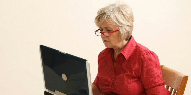 older lady on the wooden chair with the laptop
