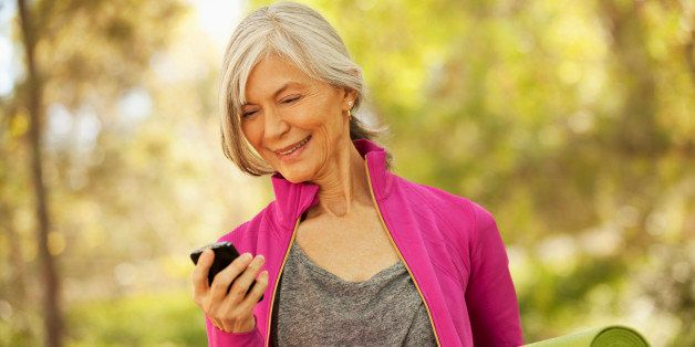 Older woman using cell phone outdoors