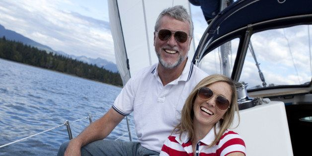 Smiling couple sitting together on a sailboat