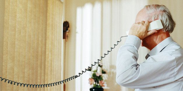 Senior man holding telephone receiver, side view