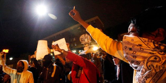 Protesters raise their hands as a circling police helicopter illuminates the area on the third night of curfew, Thursday, Apr
