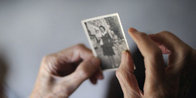 A woman, suffering from Alzheimer's desease, looks at an old picture of herself on March 18, 2011 in a retirement house in An