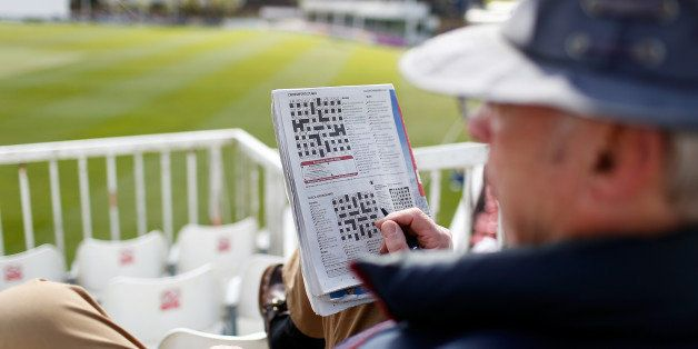 CHELMSFORD, ENGLAND - APRIL 14: A spectator does a crossword puzzle whilst watch play on day two of the LV County Championshi