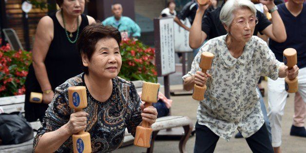 Elderly residents work out with wooden dumb-bells in the grounds of a temple in Tokyo on September 15, 2014 to celebrate Japa