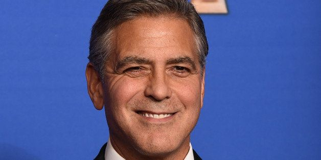 George Clooney poses in the press room with the Cecil B. Demille award at the 72nd annual Golden Globe Awards at the Beverly
