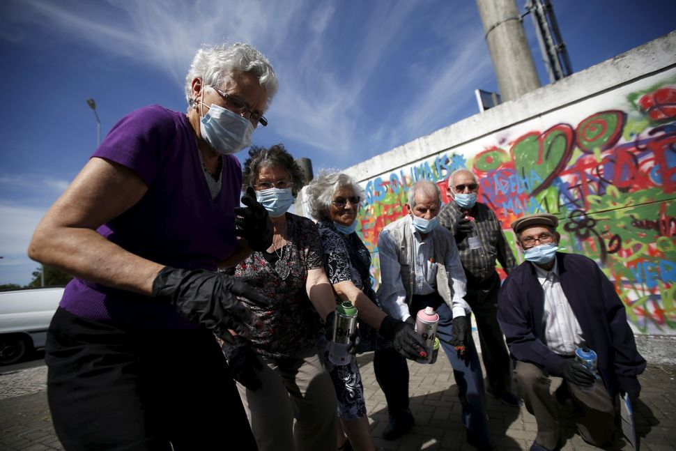 Participants pose at the end of a graffiti class offered by the LATA 65 organization in Lisbon, Portugal May 14, 2015. The LA