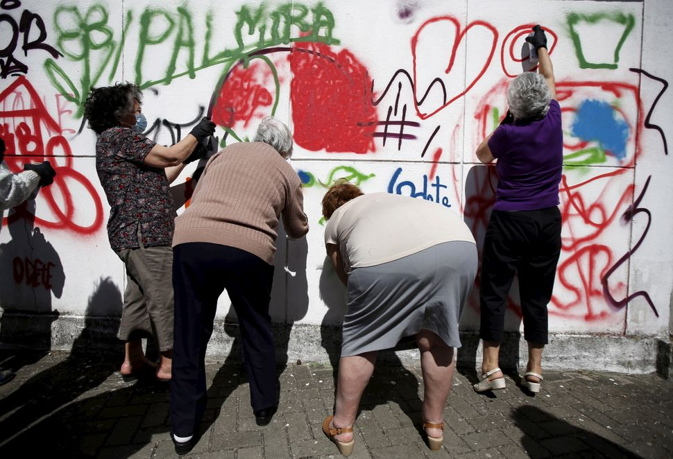 Women spray their designs on a wall during a graffiti class offered by the LATA 65 organization in Lisbon, Portugal May 14, 2
