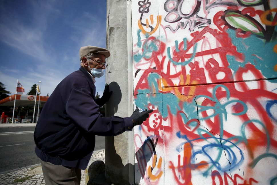 Hugo, 85, sprays on a wall during a graffiti class offered by the LATA 65 organization in Lisbon, Portugal May 14, 2015. The