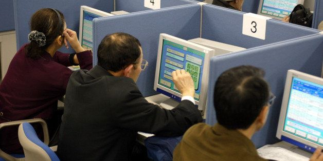 403080 01: Job seekers search for employment on computer terminals at the Hellowork employment agency March 29, 2002 in Tokyo