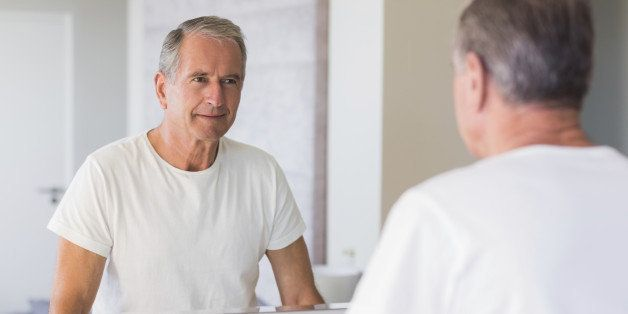 Mature man looking at his reflection in mirror in bathroom