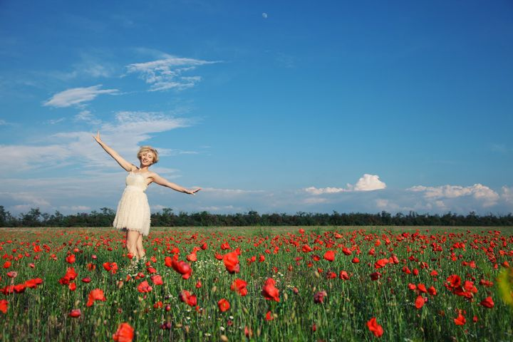 dancing girl in poppy field under blue sky