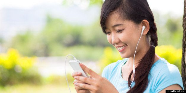 Young girl holding mp3 player in earphones on top of her head and listening music