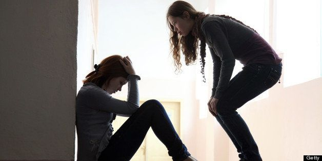 Teen girl offers to help her friend crying on the floor. silhouette