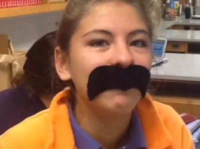 Hundreds of children sitting at desks, running around, or walking down hallways with fake, oversized facial hair: Creepy or c