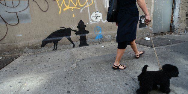 A woman walks by a street art graffiti by elusive British artist Banksy, as part of his month-long Better Out Than In exhibit