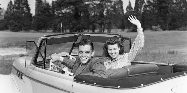 UNITED STATES - CIRCA 1940s:  Teenage couple in convertible car smile and wave to viewer.  (Photo by H. Armstrong Roberts/Ret