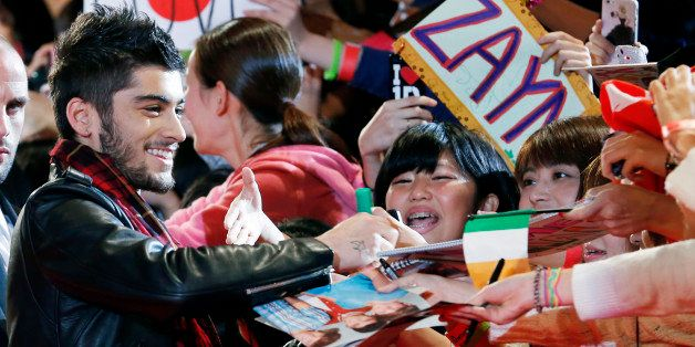 FILE - In this Sunday, Nov. 3, 2013 file photo, Zayn Malik of One Direction gives his autograph to Japanese fans during an ev