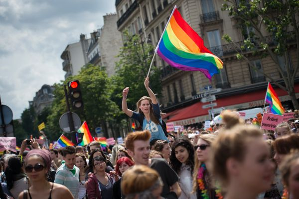 A woman holds the rainbow flag, colors of pride for the gay community during the homosexual, lesbian, bisexual and transgende