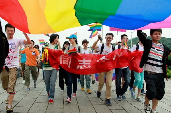 Youngsters hold a rainbow flag, a symbol for the homosexuals, as they march on the street during their anti-discrimination pa
