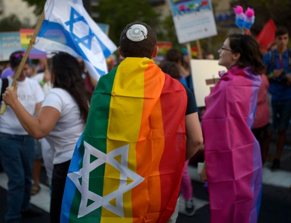 JERUSALEM, ISRAEL - SEPTEMBER 18:  Participants wear rainbow flag take part in the annual Jerusalem Gay Pride Parade 2014 in
