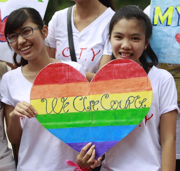 Participants pose with a rainbow coloured heart shaped placard during a local annual gay pride parade in Hanoi on August 4, 2