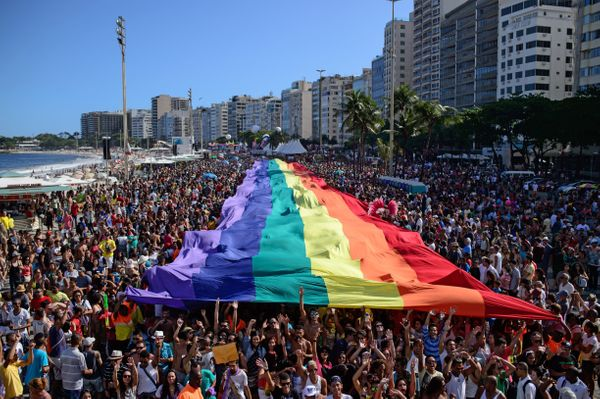 Revellers march with a giant rainbow flag during the annual Gay Pride Parade at Copacabana beach in Rio de Janeiro, Brazil, o