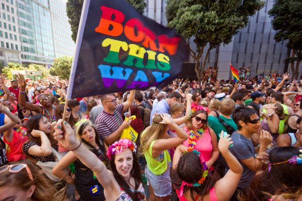 Woman waving a 'Born this Way' rainbow flag over the dancing crowd in front of the San Francisco Federal Building, at the Gay