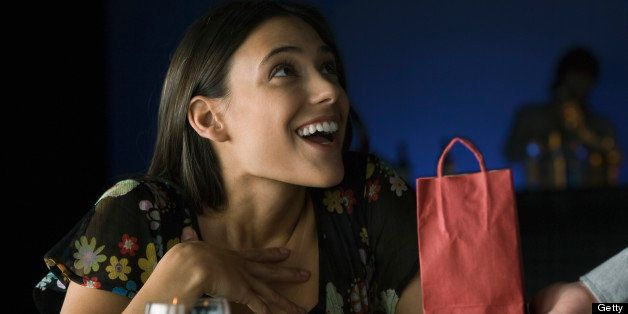 Woman being presented with gift, looking up in astonishment at giver
