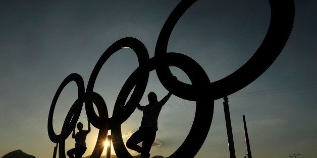 People pose for a photo with the Olympic Rings at the Olympic Park in Rio de Janeiro, Brazil, Monday, Aug. 1, 2016. The Summe