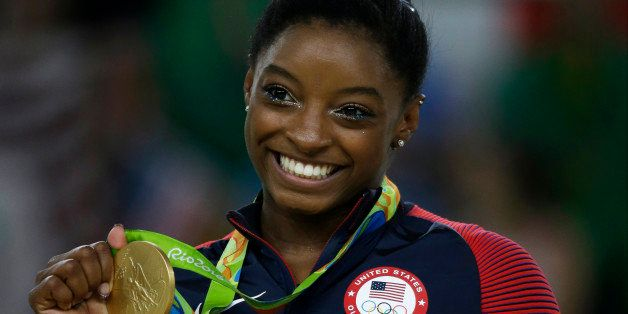 United States' Simone Biles displays her gold medal for floor during the artistic gymnastics women's apparatus final at the 2