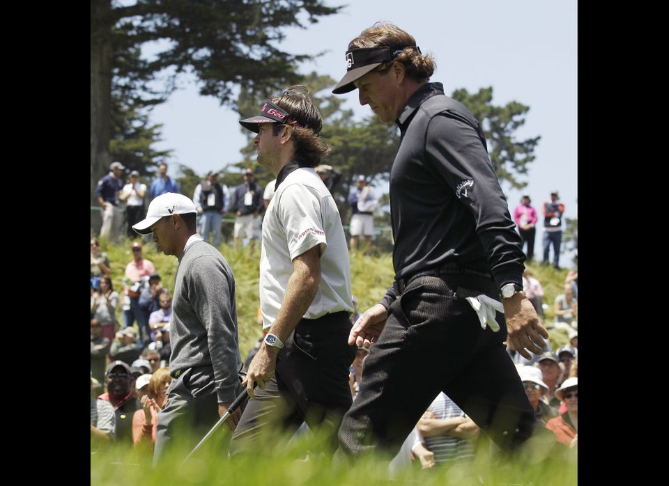 Tiger Woods, left to right, Bubba Watson and Phil Mickelson walk up the 18th hole during the first round of the U.S. Open Cha