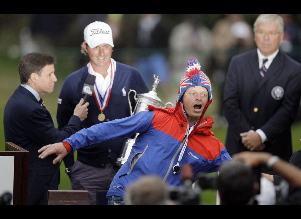 A fans runs in front of Webb Simpson as he is interviewed after the U.S. Open Championship golf tournament Sunday, June 17, 2