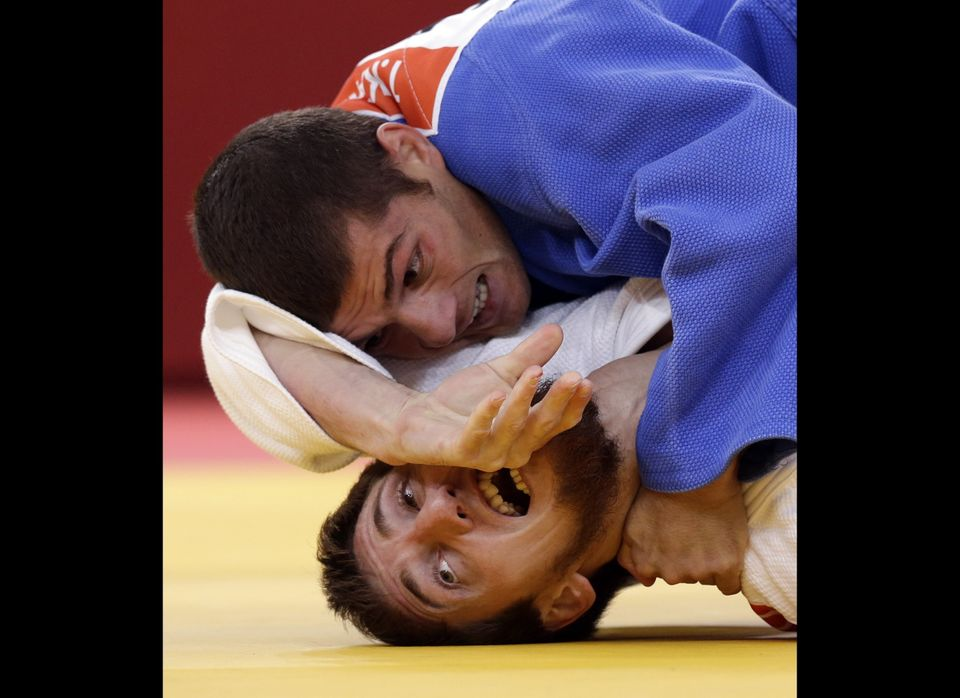 Tarlan Karimov of Azerbaijan (in blue) competes against Musa Mogushkov of Russia during the men's -66kg judo competition at t