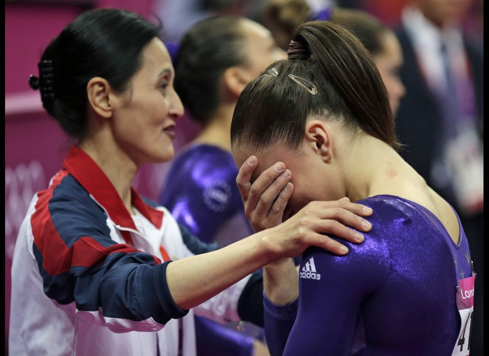 Coach Jenny Zhang consoles U.S. gymnast Jordyn Wieber as she cries after failing to qualify for the women's all-around finals