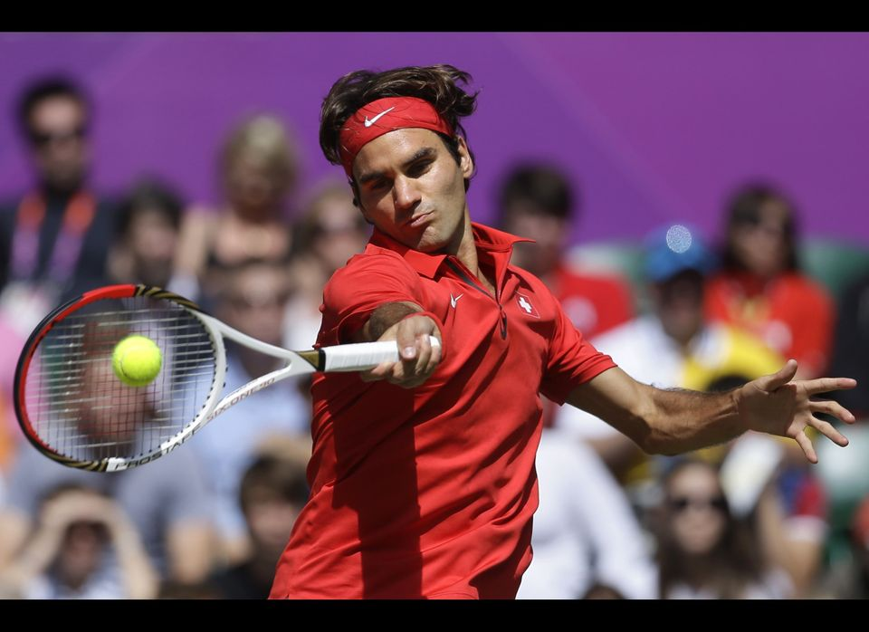 Switzerland's Roger Federer returns a shot to Britain's Andy Murray during the men's singles gold medal match at the All Engl
