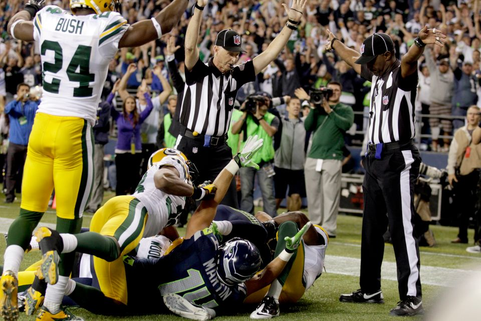 Officials signal a touchdown by Seattle Seahawks wide receiver Golden Tate, obscured, on the last play of an NFL football gam