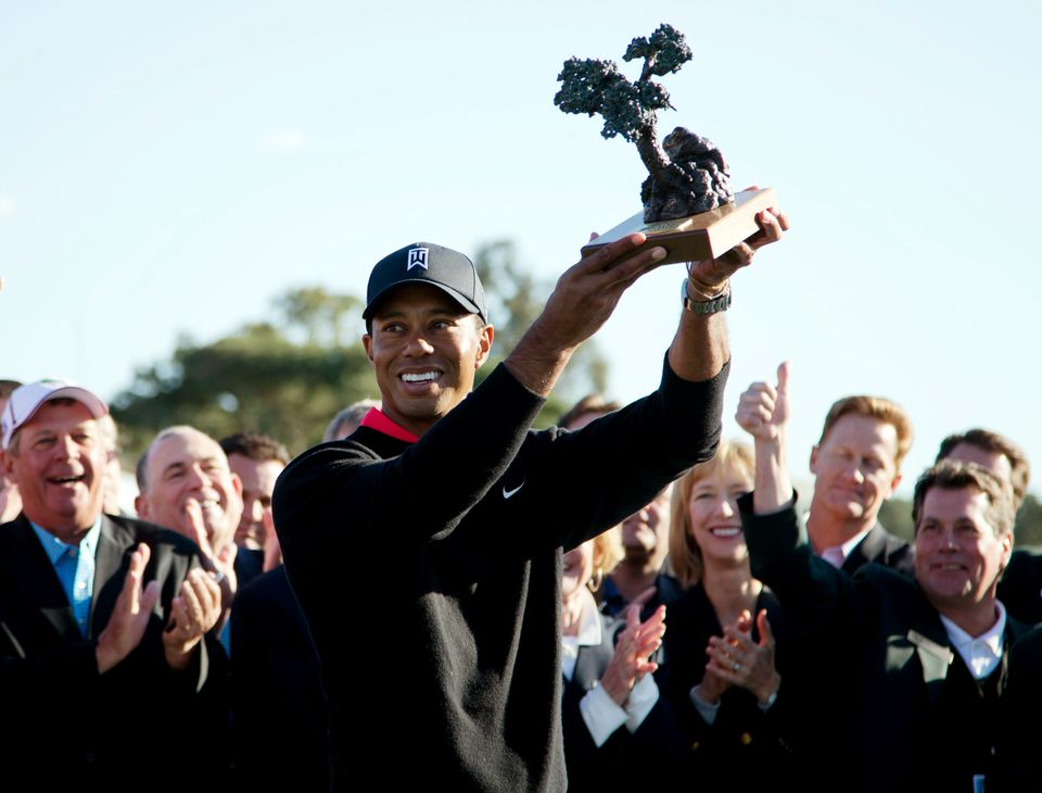 Tiger Woods holds up the trophy after winning the Farmers Insurance Open golf tournament at the Torrey Pines Golf Course, Mon