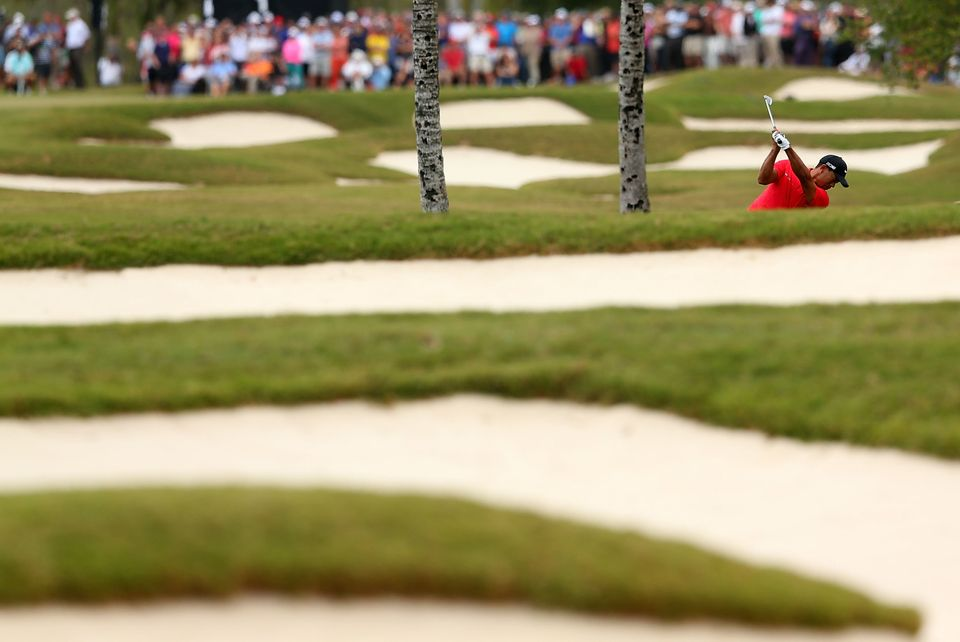 DORAL, FL - MARCH 10:  Tiger Woods plays a shot from the rough on the first hole during the final round of the World Golf Cha