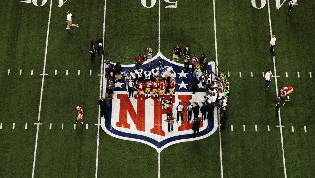 NEW ORLEANS, LA - FEBRUARY 03:  Players from the San Francisco 49ers and the Baltimore Ravens stand on the NFL logo for the o