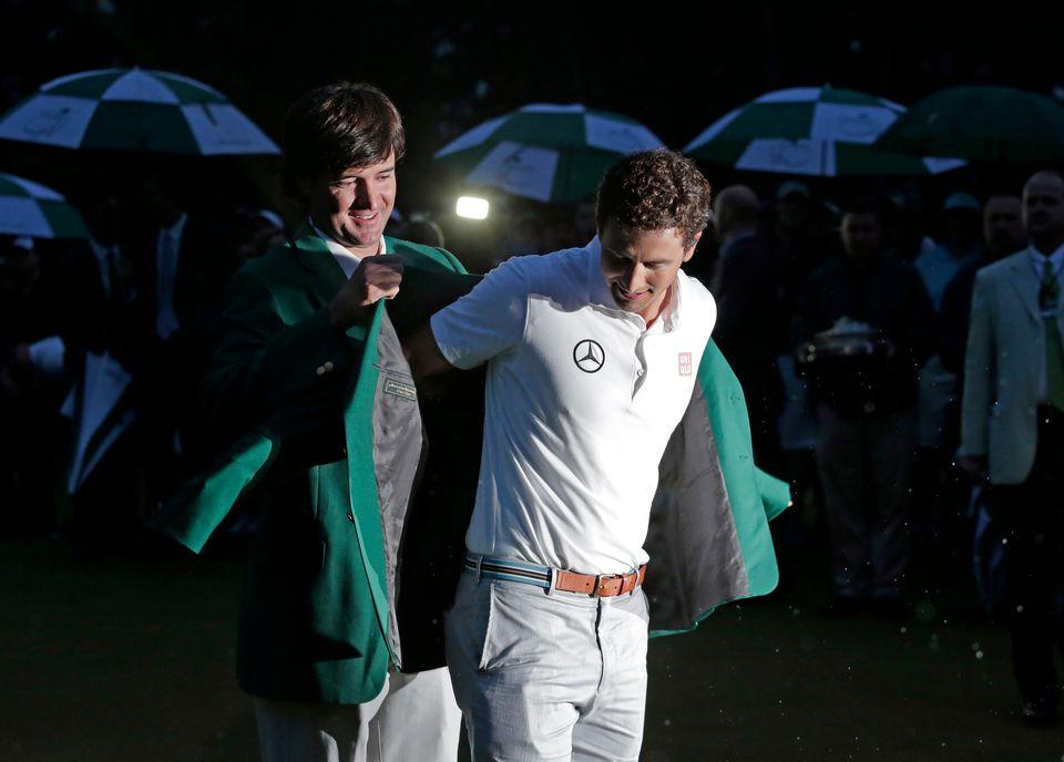 Bubba Watson, left, helps Adam Scott, of Australia, put on his green jacket after winning the Masters golf tournament Sunday,