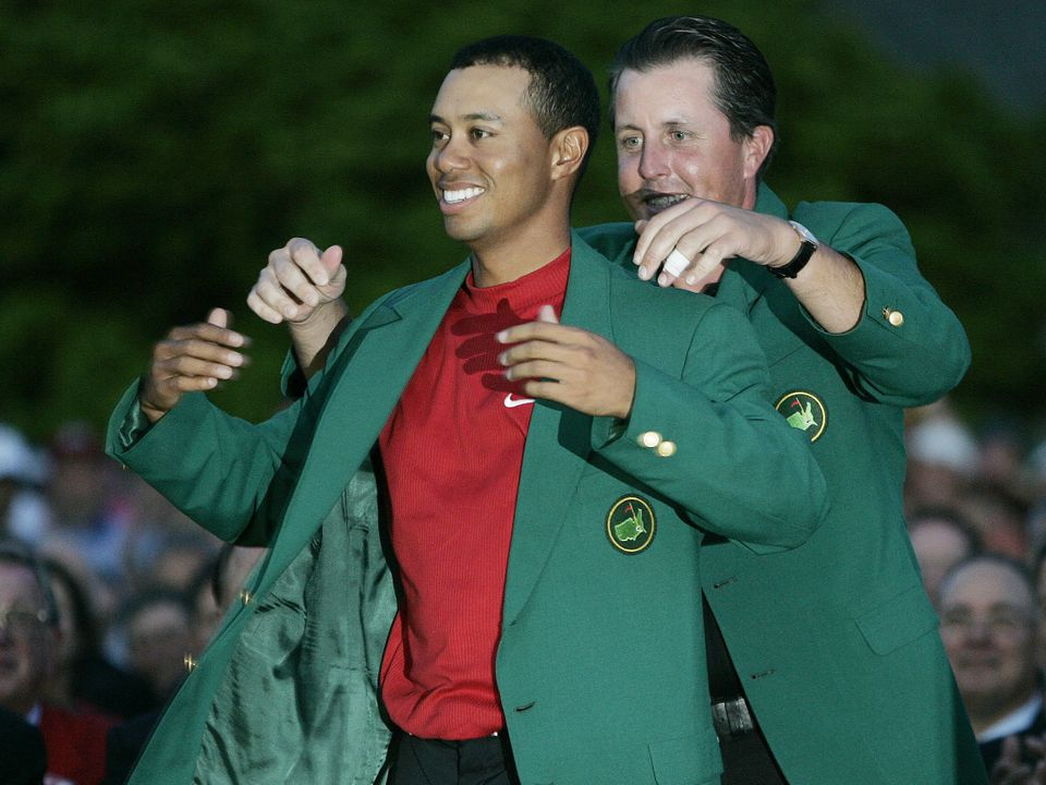 This April 10, 2005, file photo shows Tiger Woods, left, getting the Green Jacket from Phil Mickelson, right, after winning t