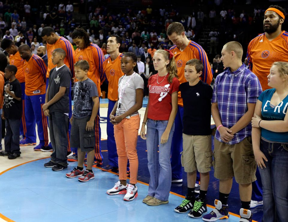 New York Knicks players and children bow their heads in a moment of silence for the victims of the explosions at the Boston M