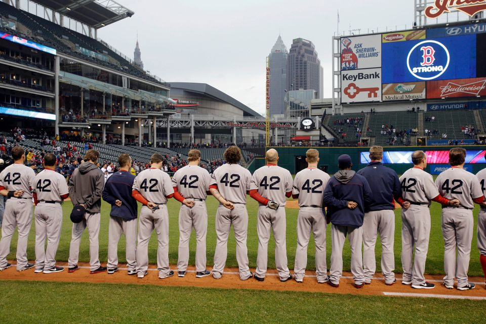 The Boston Red Sox players and coaches observe a moment of silence for the victims of the Boston bombings before a baseball g