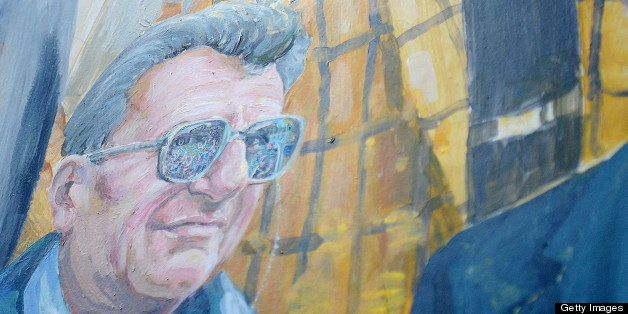 Artist Michael Pilato painted over the halo above Joe Paterno's head on the mural on Hiester Street in downtown State College